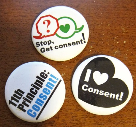 "3 buttons. One says: ""Stop, Get Consent!"" one says ""11th Principle: Consent"" and the third says ""I heart consent!"""