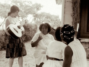 Heather Tobis Booth playing guitar for Fannie Lou Hamer during the Freedom Summer Project in Mississipi, 1964. Copyright Wallace Roberts.