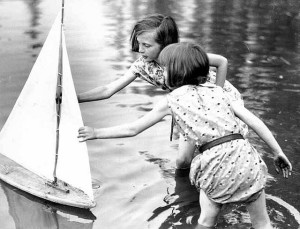 Two children release a toy sailboat