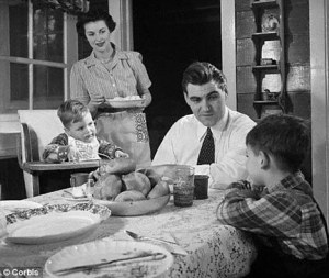 A woman serves dinner to a man and two children in an image of a conservative 1950's household.