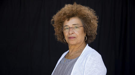 Photograph of Angela Y. Davis against a black curtain background