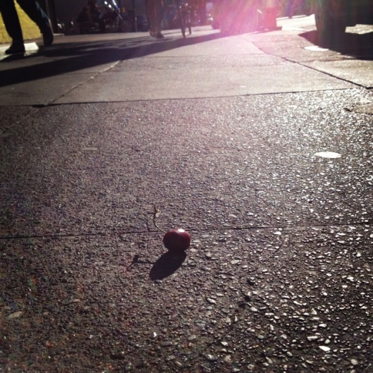 single cherry (fruit) sitting on the sidewalk