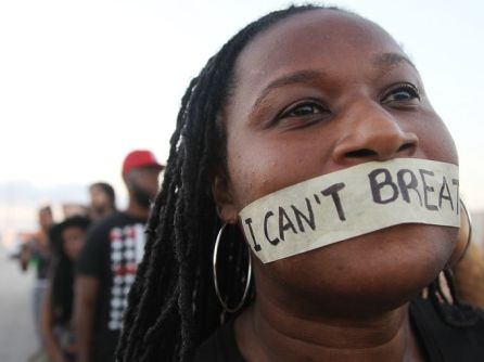 "A Black woman with tape over her mouth on which the words ""I can't breathe"" are written"