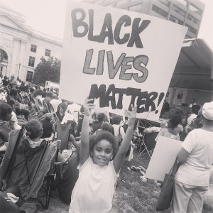 "a child holds a sign that says ""Black Lives Matter""- with other protesters in the background. Black and white photo."