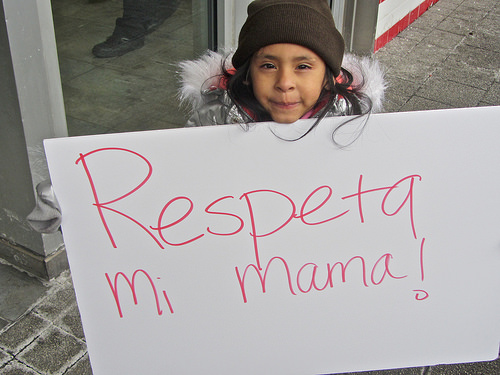 "a child in a hat and coat holds a sign that says ""Respeta mi mama!"