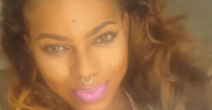 Photo of Zella Ziona, a black trans woman with a septum ring, pink lipstick, and long curly hair. She is smiling with her lips closed.
