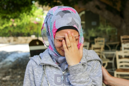 A woman puts her hand over her face. She is crying. She wears a gray sweatshirt, gray and pink star-patterned headscarf, and wedding band. She is in a park.